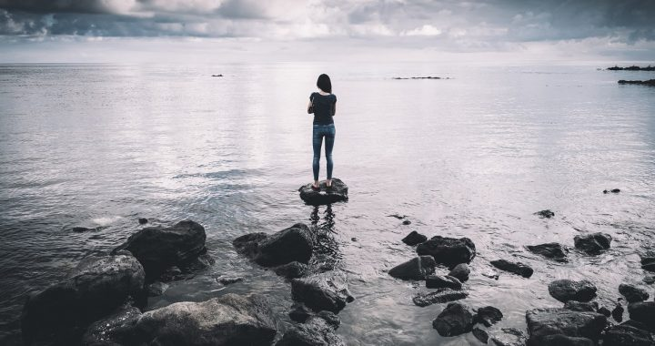 Lost - woman standing in the water on a rock
